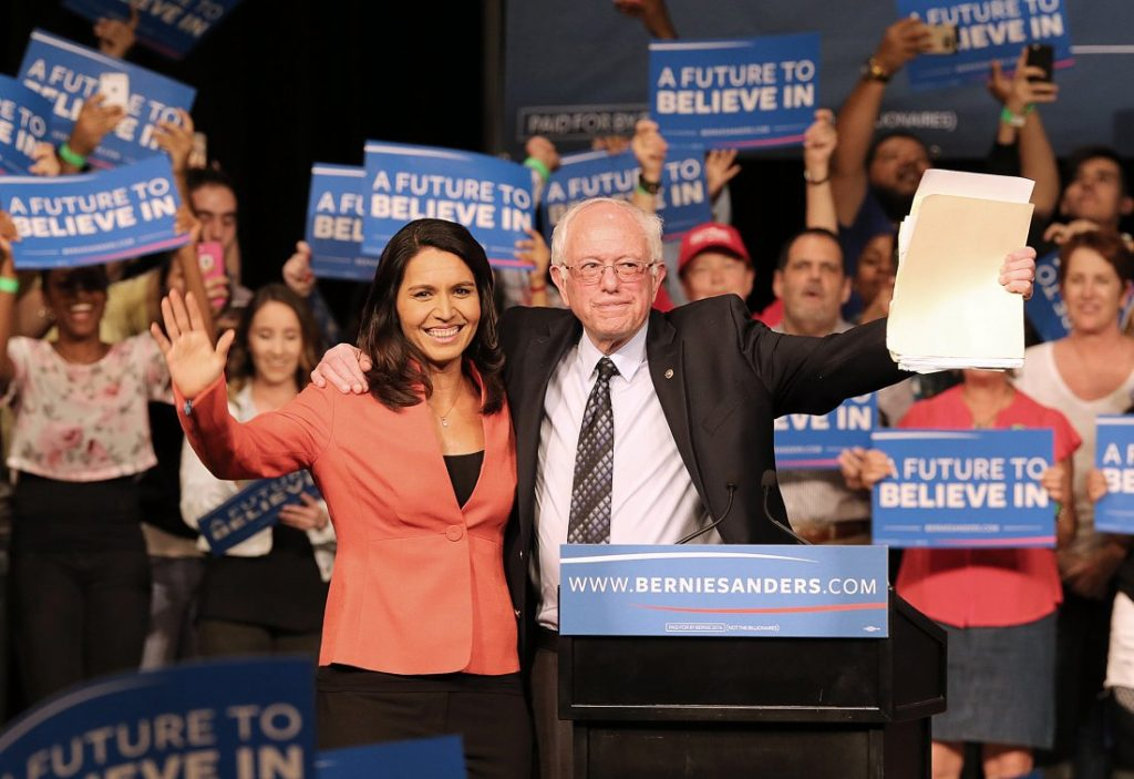 Rep. Tulsi Gabbard, D-Hawaii, and Democratic presidential candidate Sen. Bernie Sanders wave to supporters during a campaign event in Miami at the James L. Knight Center on Tuesday, March 8, 2016. (Pedro Portal/El Nuevo Herald/TNS via Getty Images)
