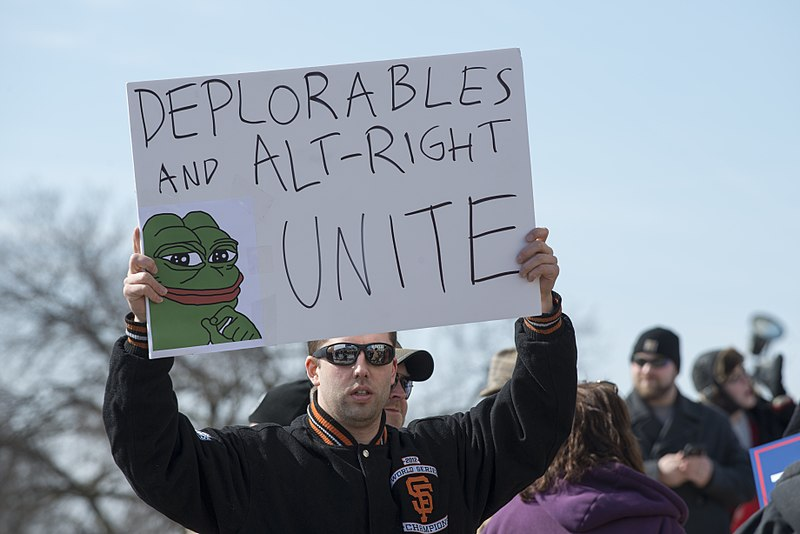 A Unite the Right rally attendee with a pepe meme poster. (Source: Wikimedia)