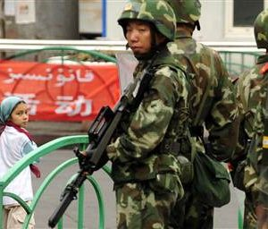 Chinese military personnel stand in front of sign in both Arabic and Chinese. Source: East Turkistan Australian Association