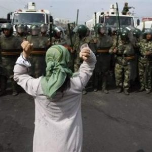 Uighur woman stands in opposition to Chinese military. Source: East Turkistan Australian Association
