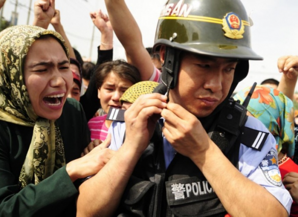 A Han Chinese policeman turns his back upon Uyghers' cries of protest.