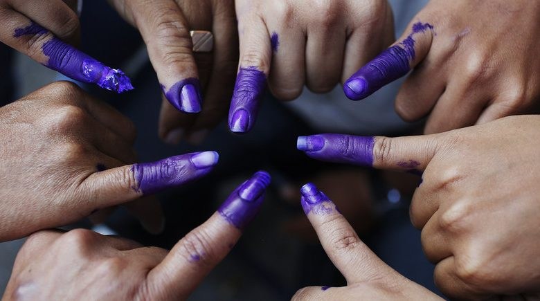 A group of people painting their pinkies purple in consolidation behind democracy. Source: REUTERS/Tomas Bravo