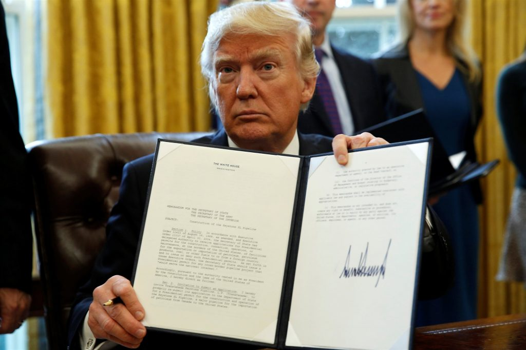 President Donald Trump holding up one of many executive orders signed during his first month in the White House. Source: REUTERS / Kevin Lamarque
