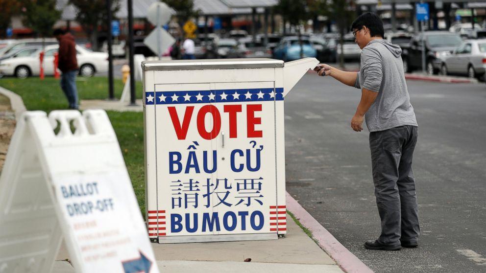 Man drops ballot in ballot box with various language translations.
